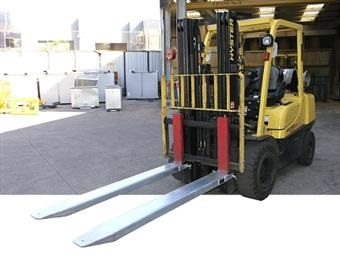Yellow forklift fitted with a pair of forklift extension slippers.